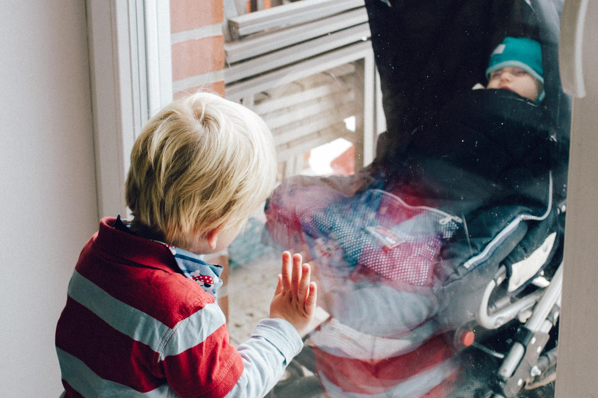 Familienreportage Berlin: blonder Junge in rot gestreiftem Pullover schaut aus dem Fenster vor dem ein Baby im Kinderwagen schläft