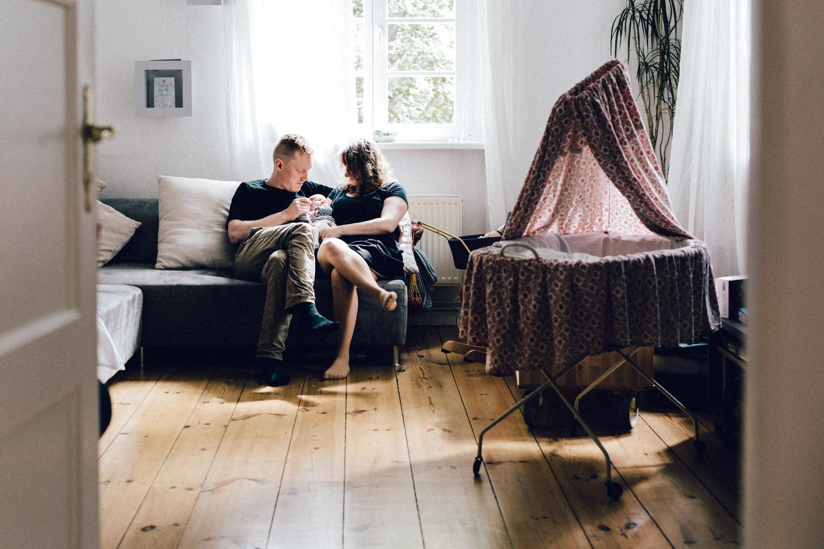 Familienreportage Neugeborenenfotos Berlin: Paar sitzt mit Baby auf Couch in Berlin-Wedding. Daneben: Stubenwagen