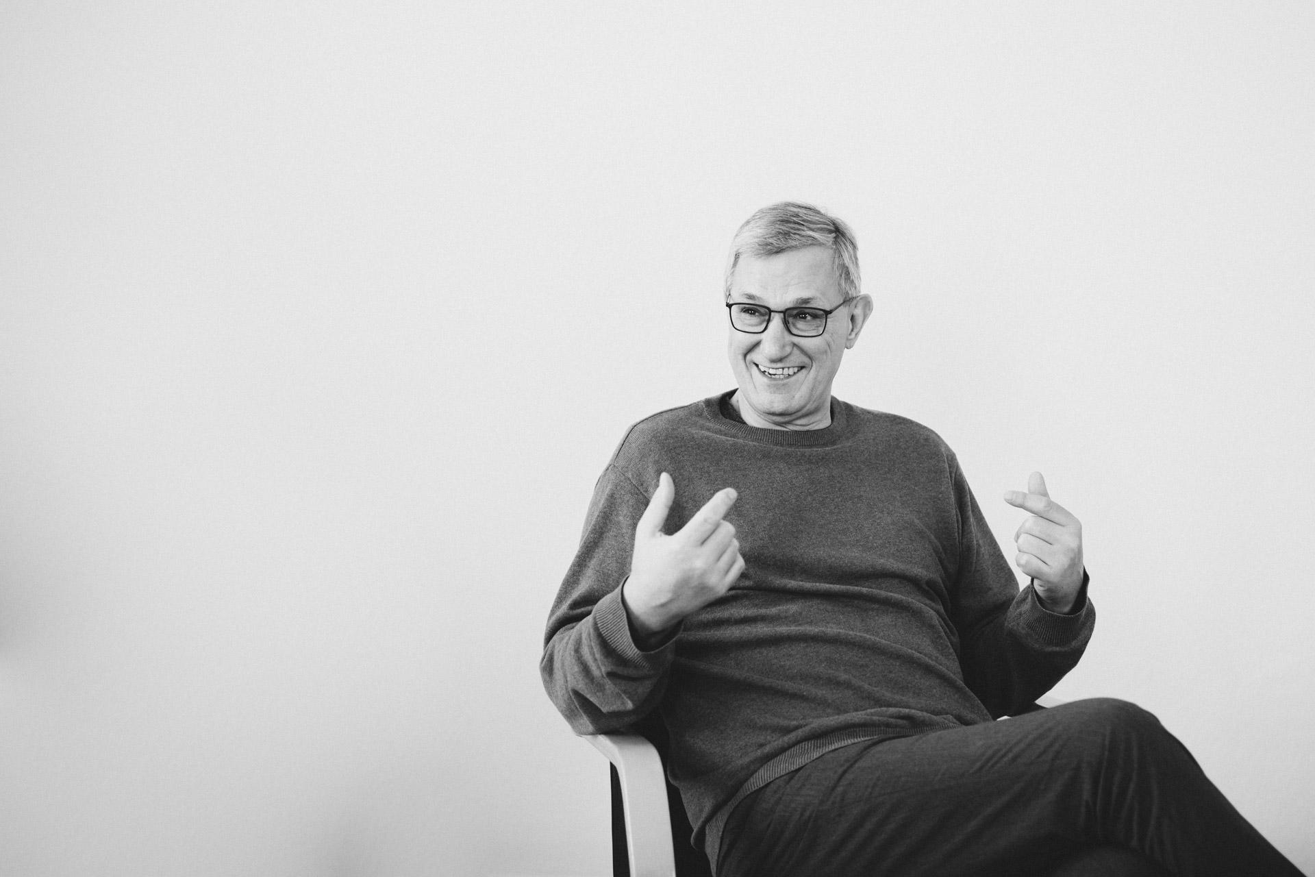 Schwarzweißfoto Bernd Riexinger sitzend vor Weißer Wand